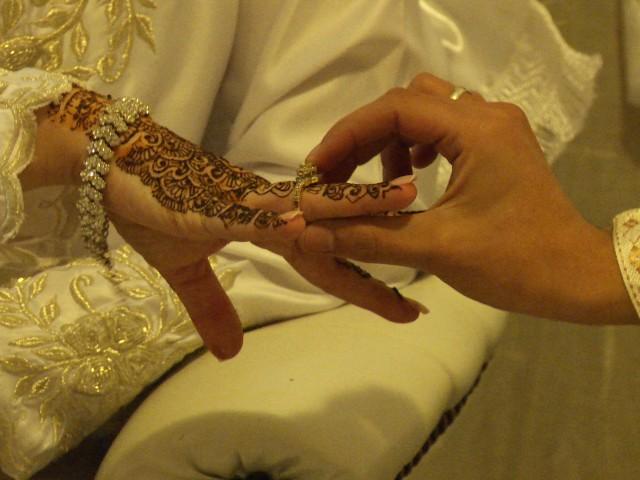 een (trouw?)ring wordt geschoven aan een met henna beschilderde hand van een bruid